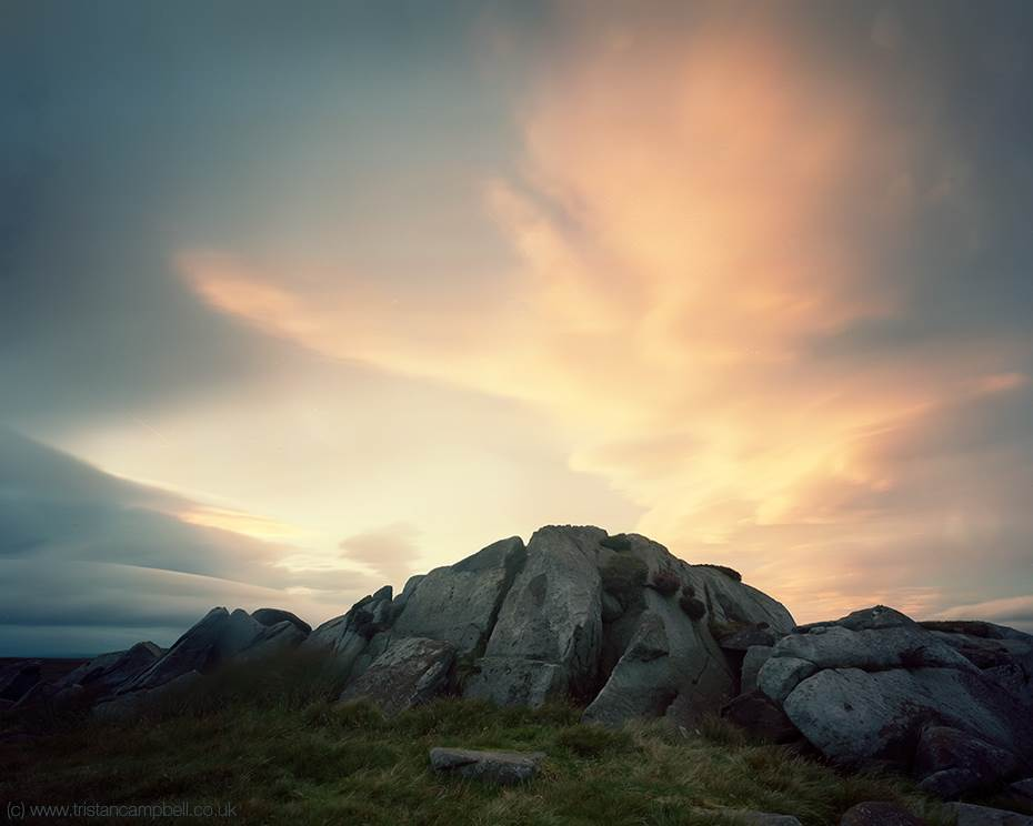 Amazing high clouds rise above a moorland outcrop providing a dramatic sky